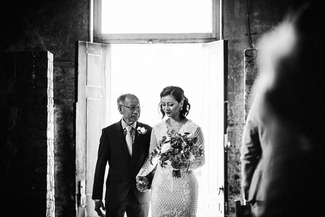 bride enters ceremony with her dad at the asylum chapel