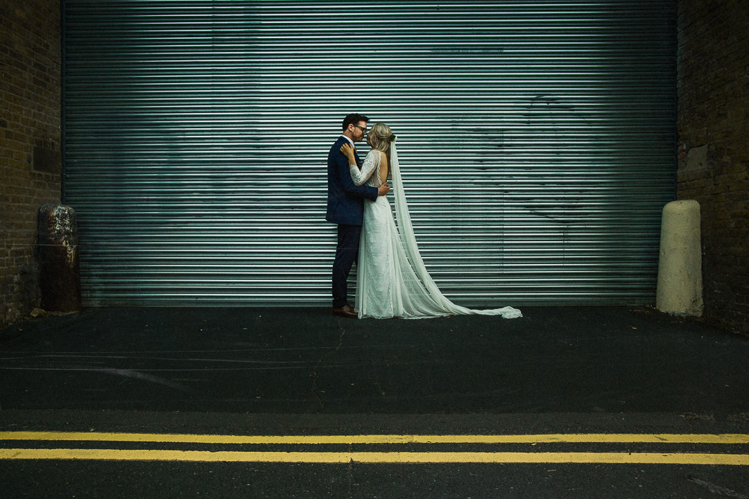 wedding photograph or couple stood against loading bay with yellow lines in foreground