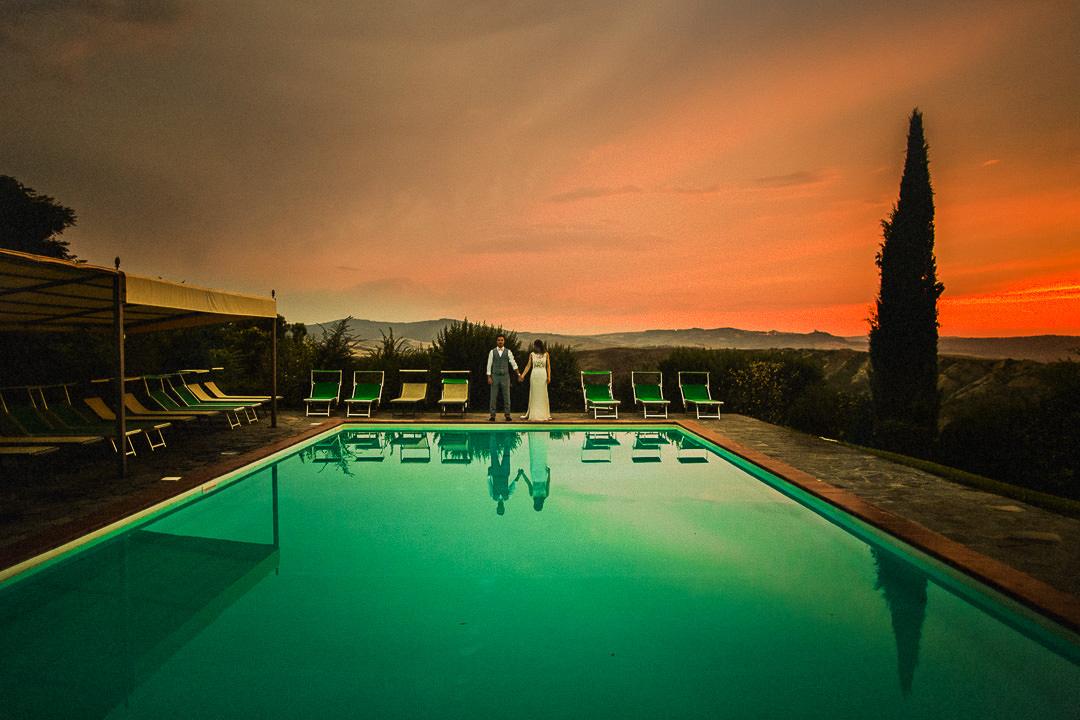 Tuscany wedding photograph of couple stood poolside