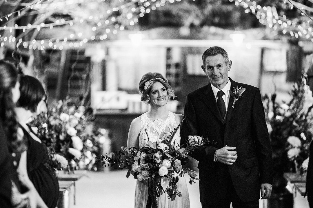 bride walks down the aisle with her day at The Tithe Barn with a backdrop of fairy lights