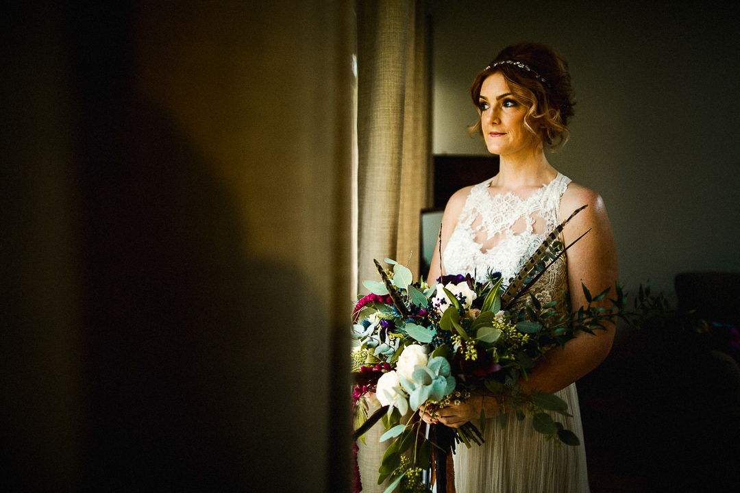 bride portrait next to a window in the tythe barn before her wedding ceremony