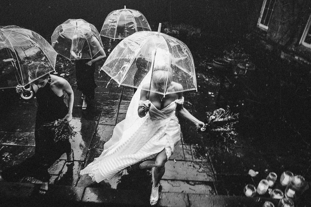 wedding photo of bride running in the rain in Hayley Paige gown