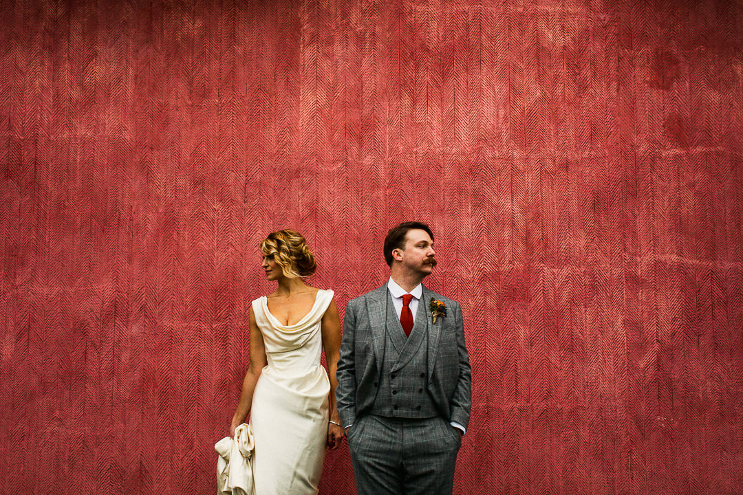 alternative wedding photograph of bride and groom against pink background