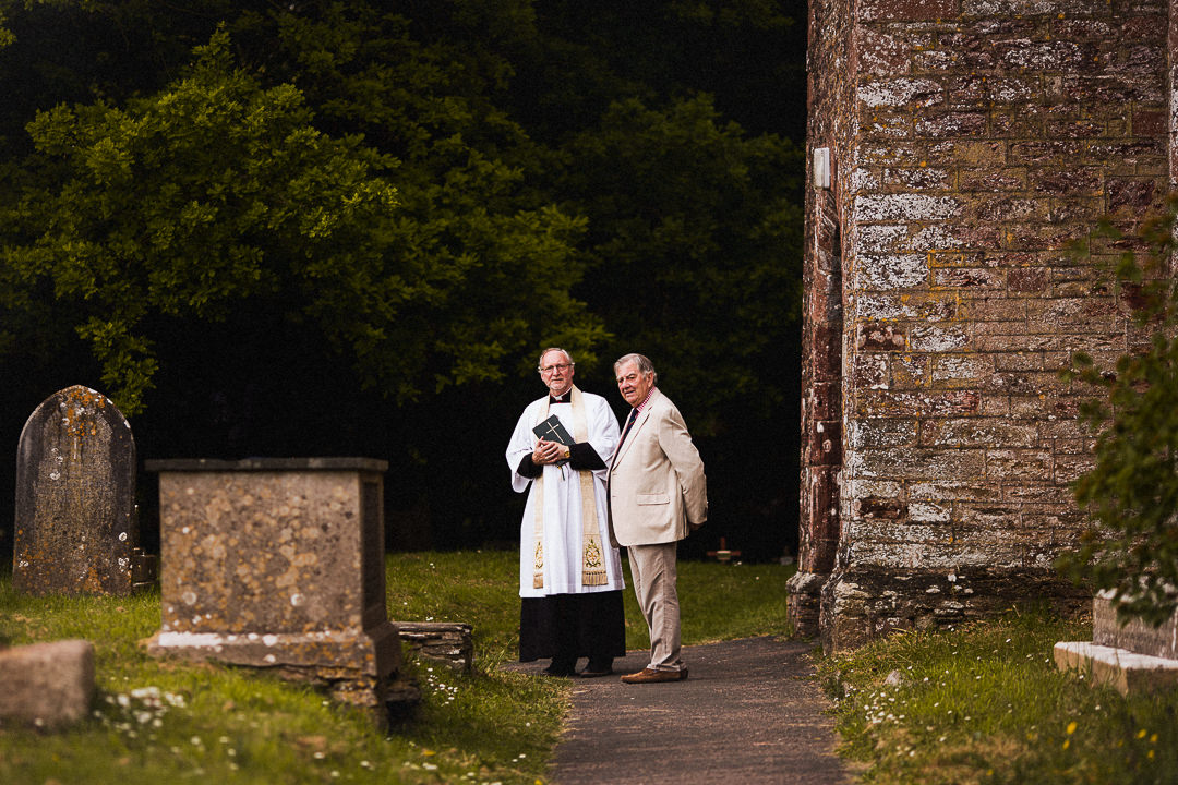 vicar and verger outside of wedding chapel