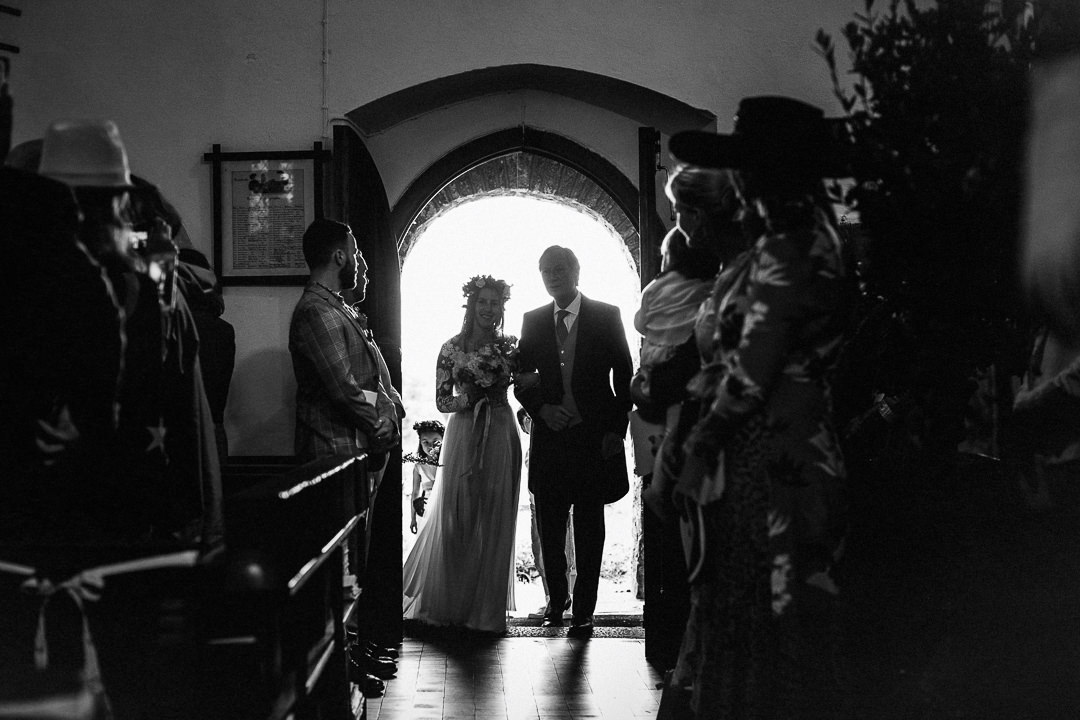 bride and her dad stood in doorway of church