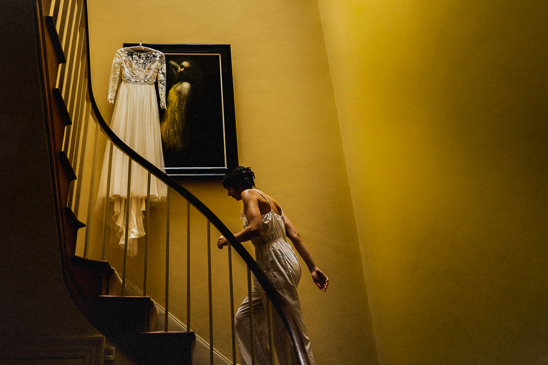 the wedding dress hung on an art work with bridesmaid walking upstairs