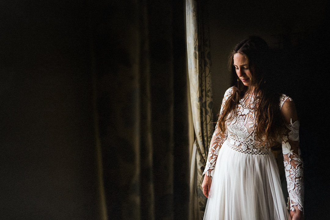bride stood in window light just after dress is put on