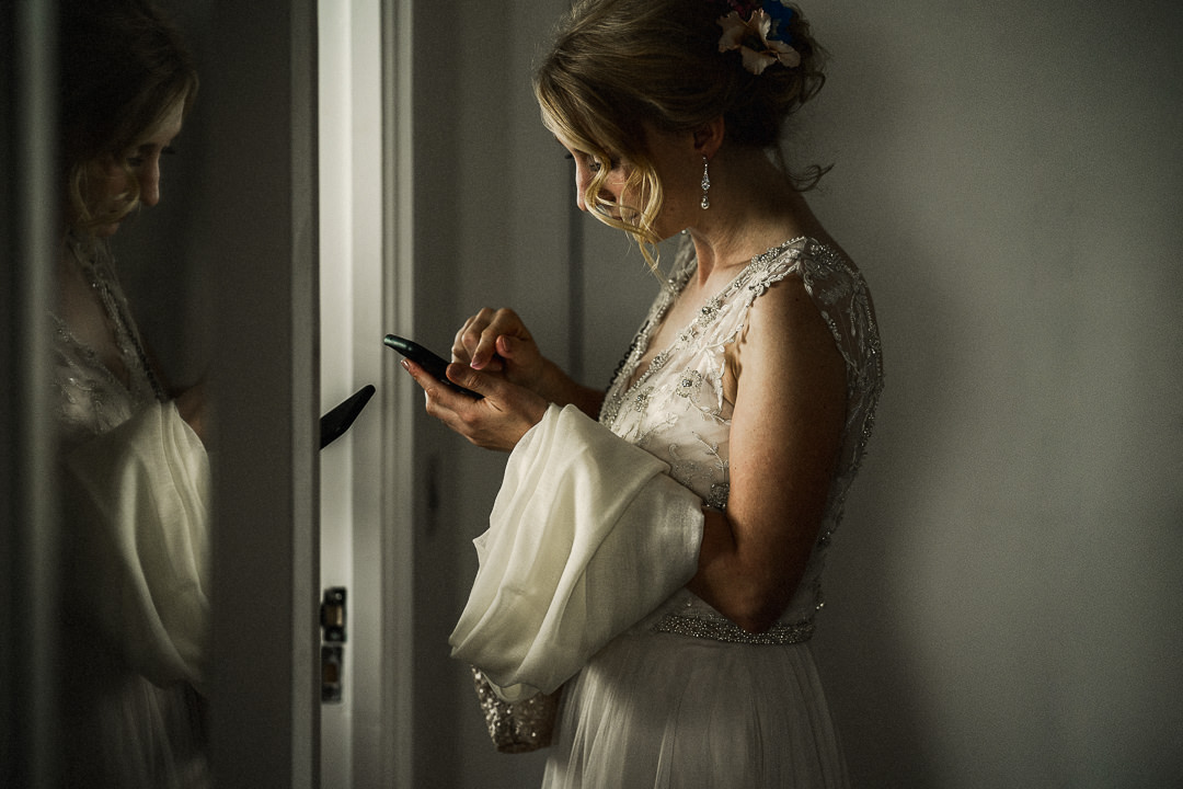 bride in wedding dress awaits confirmation of taxi to take her to wedding ceremony