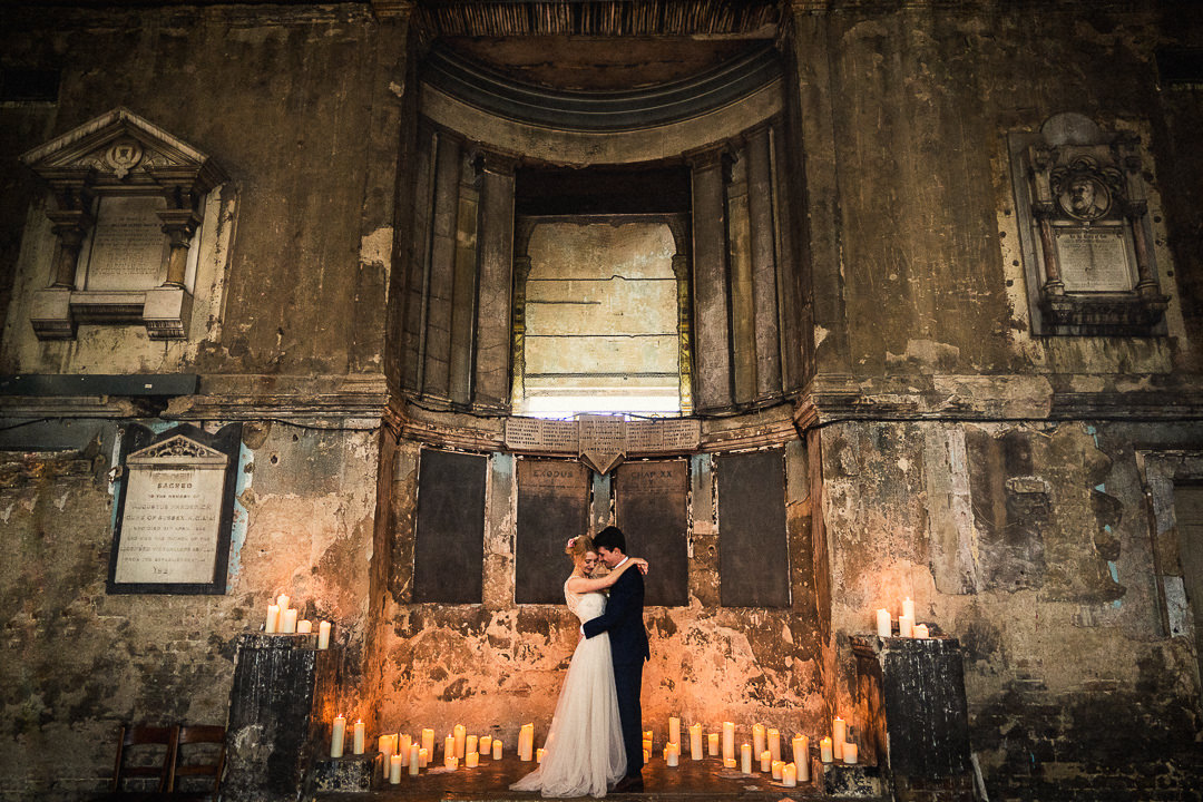 bride and groom in romantic embrace stood on the candlelit stage at the asylum chapel