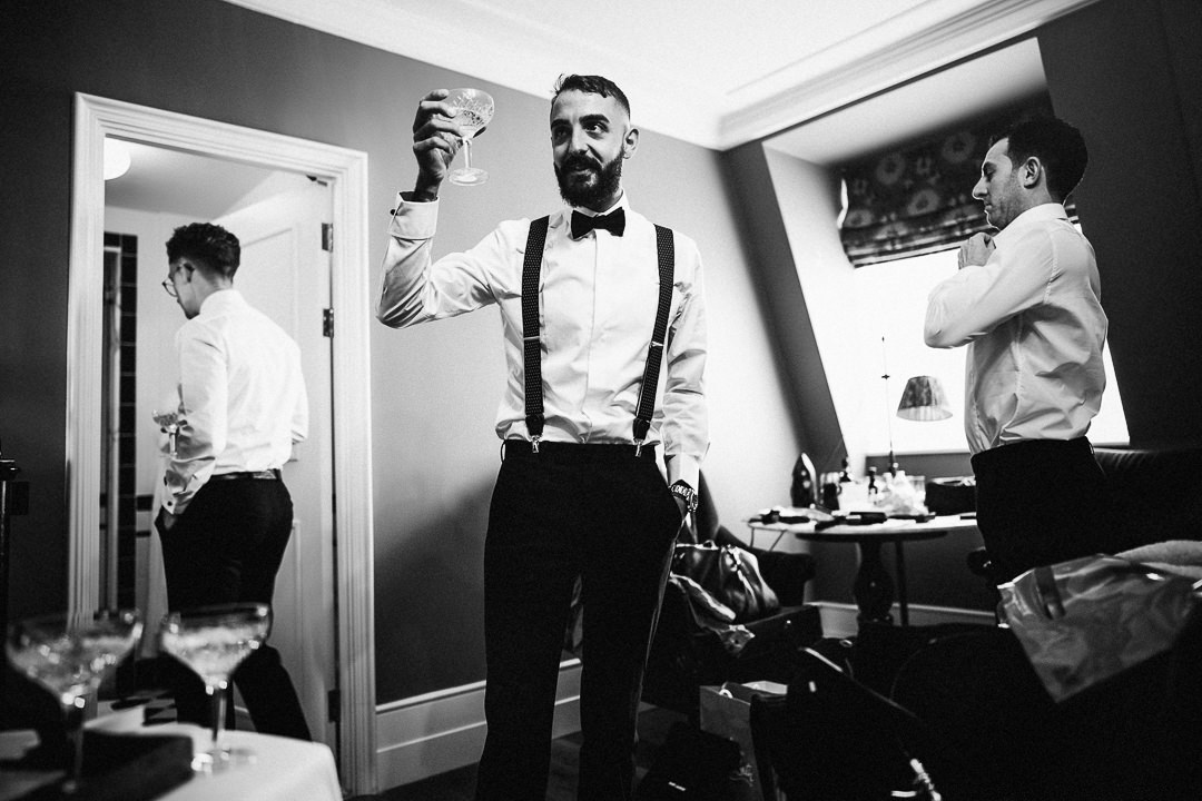 bestman raises a champagne toast to the groom