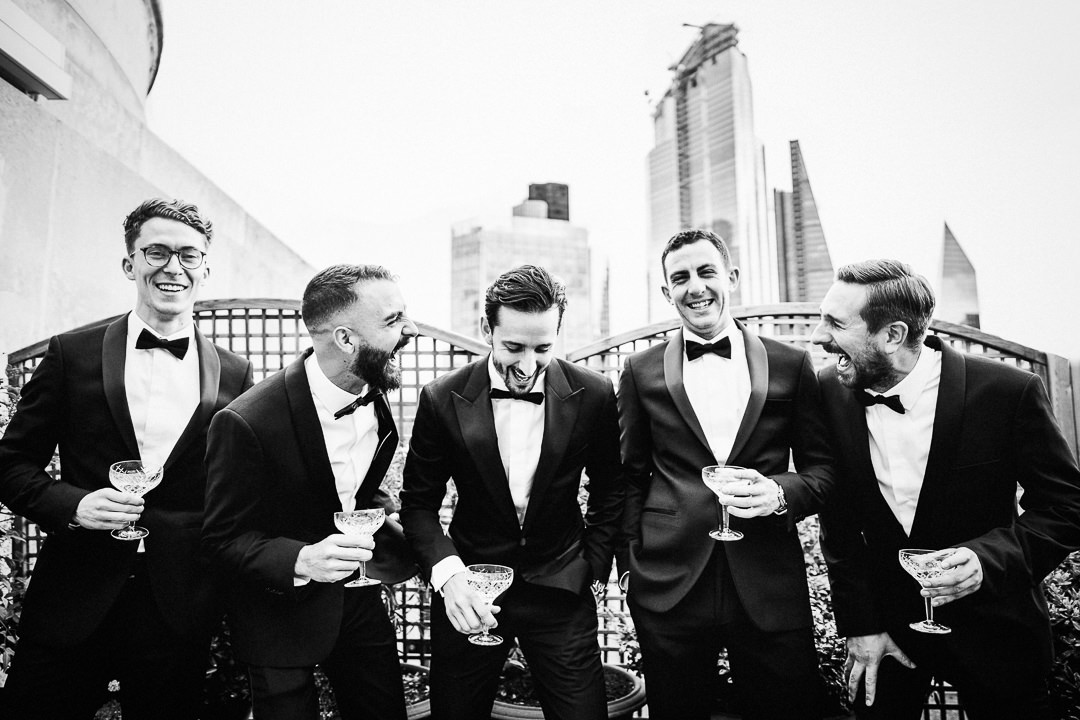 a groom and groomsmen groups shot with modern city backdrop