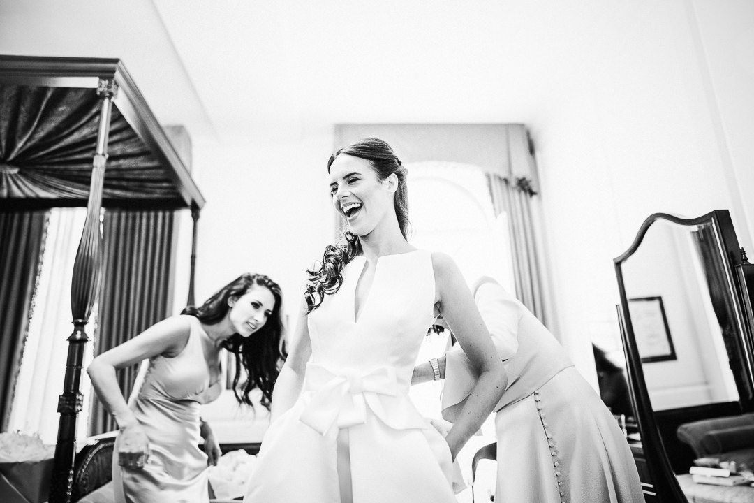 bride laughs as her bridesmaids get her into her Jesus piero wedding dress