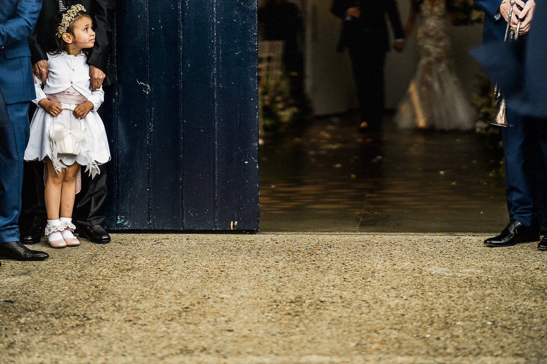 flower girl awaits bride and groom for confetti throw