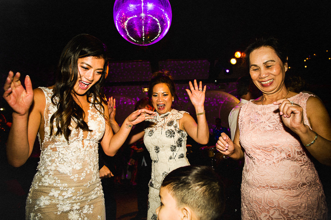 bride and mother of the bride dancing below a mirror ball