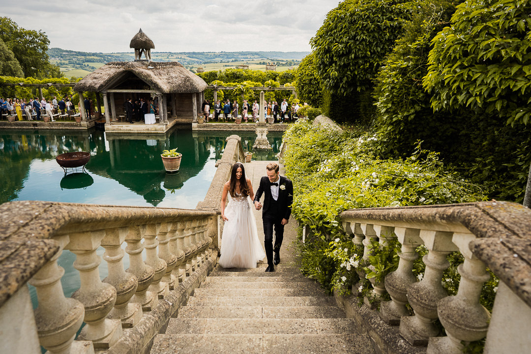 bride and groom exit their wedding ceremony with the boathouse and Wiltshire countryside beyond