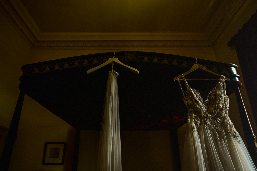 A wedding dress and veil hang in soft light at euridge manor