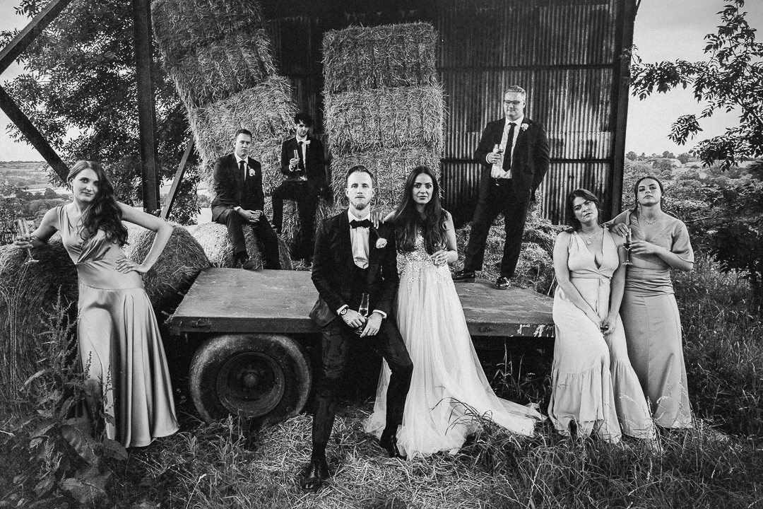 a wedding party group shot in an abandoned hay barn