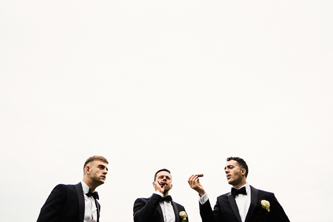 groom and friends smoke cigars
