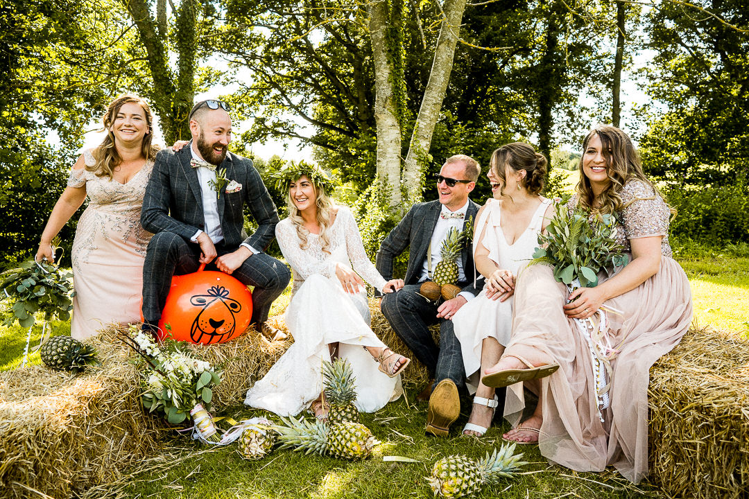 a wedding party groups shot on hay bails
