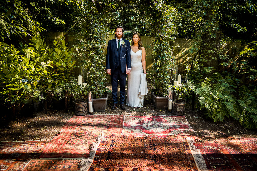 A modern bride and groom wedding photography portrait with greenery and vintage rugs