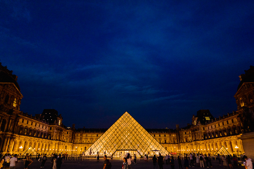 a nighttime scene setting shot of the lit louvre pyramid in Paris