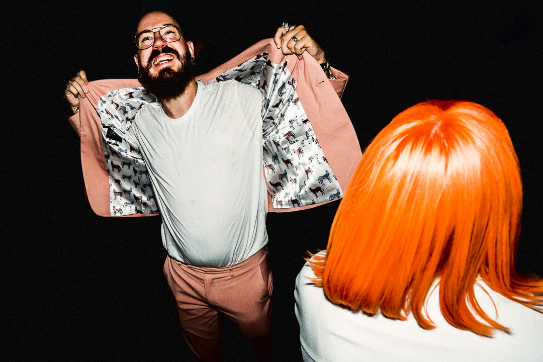 A dancefloor image of 2 guests in a pink suit and with orange hair