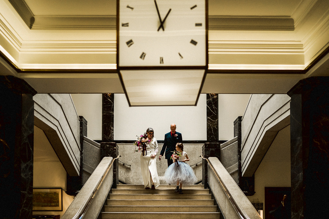 bride, flower girl and father of the bride come down the staircase at the townhall hotel