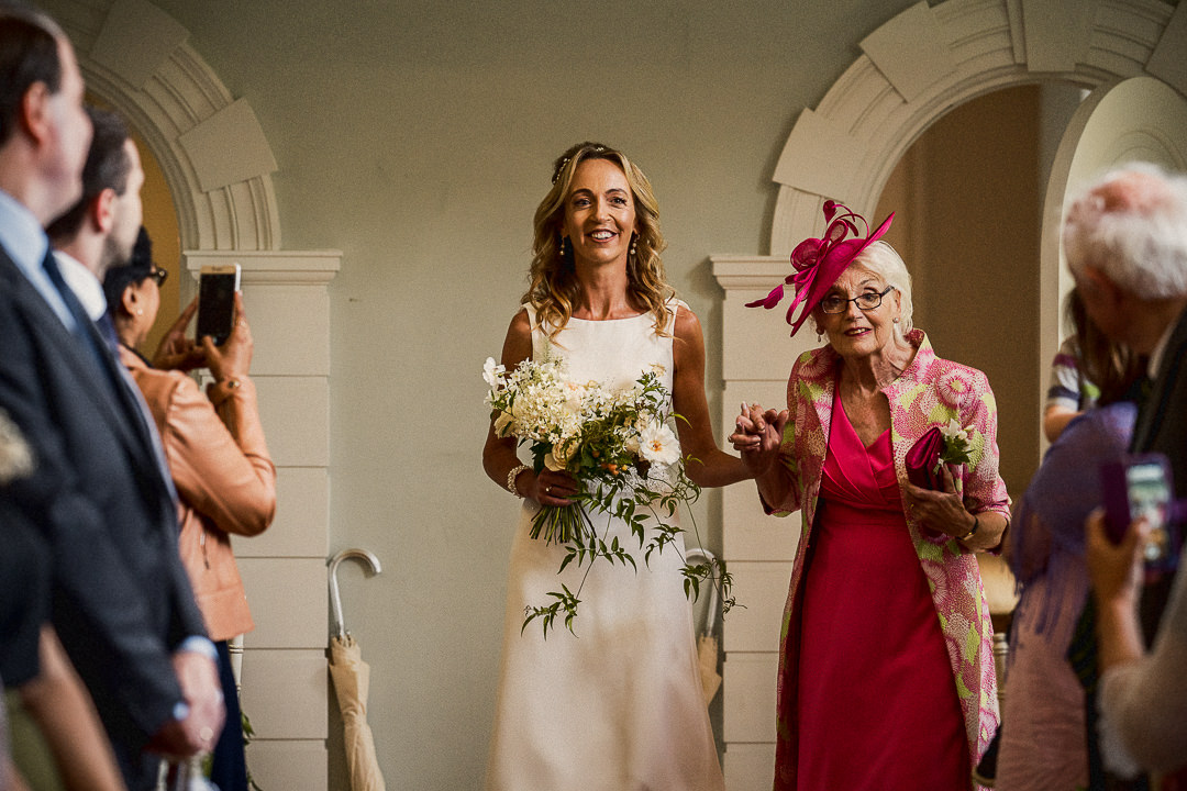 bride enters ceremony room smiling accompanied by her mum