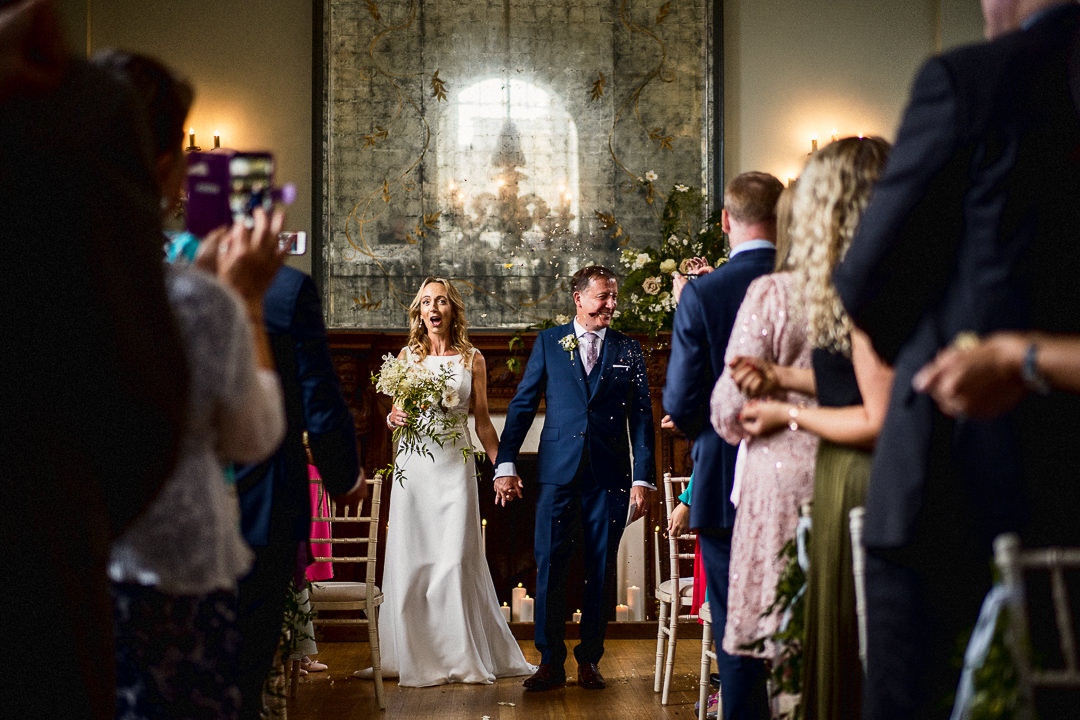 bride and groom exit as husband and wife as guests throw confetti