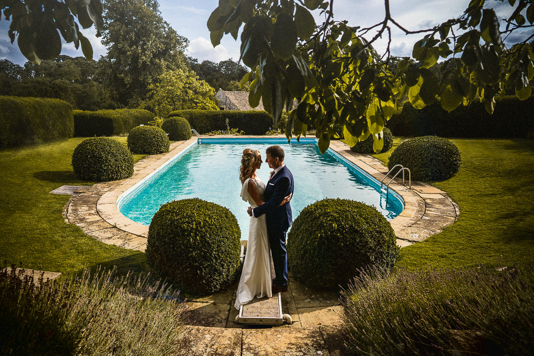 bride and groom portrait next to Cornwall manors swimming pool