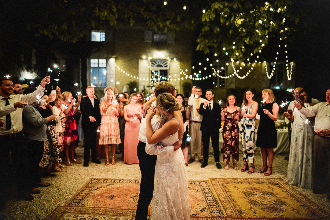 A first dance, outside on vintage rugs beneath fairy lights at Chateau Lartigolle