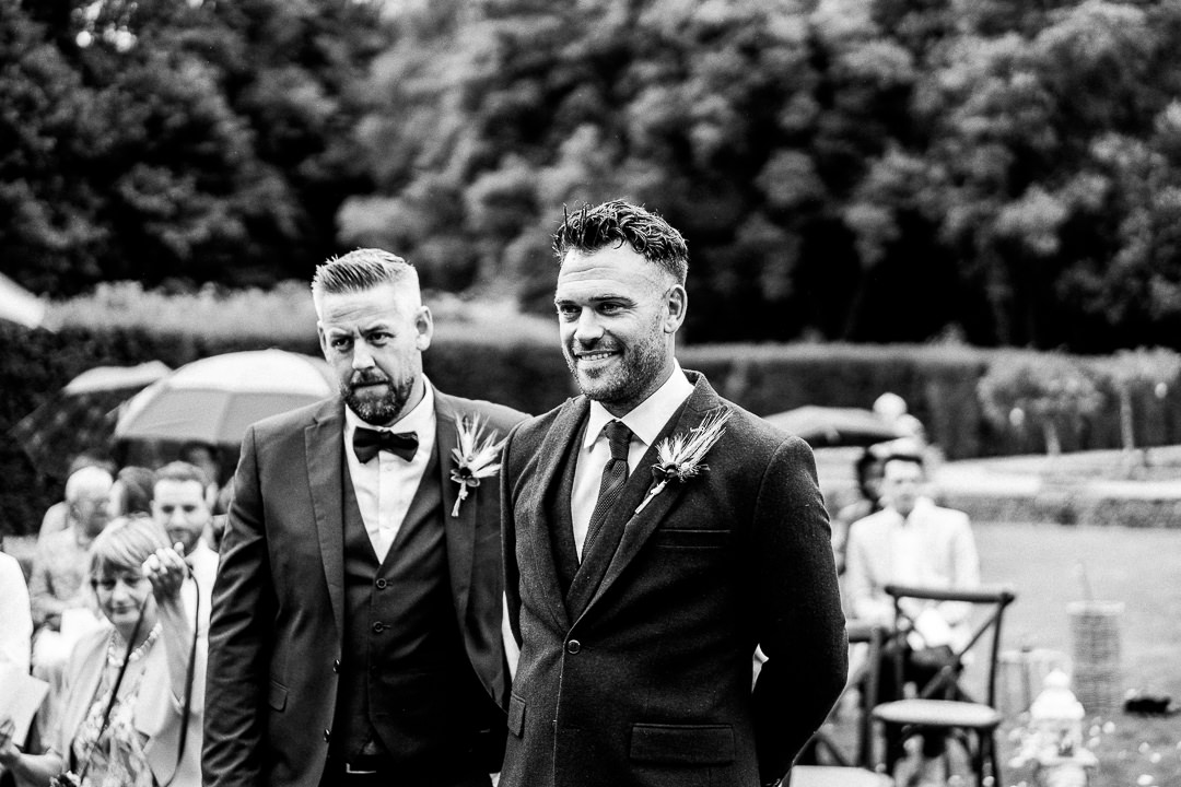 groom awaits the arrival of the bride with his best man at an outdoor ceremony at voewood wedding venue