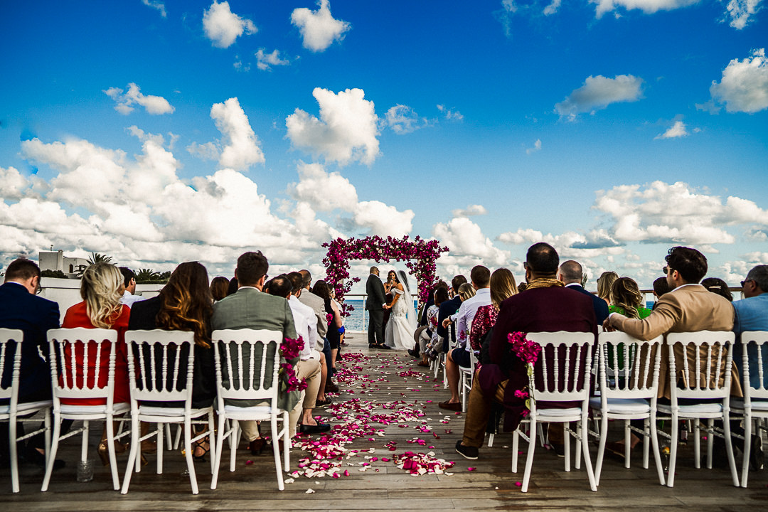 a wide shot of a rooftop ibiza wedding ceremony with blue skies and clouds