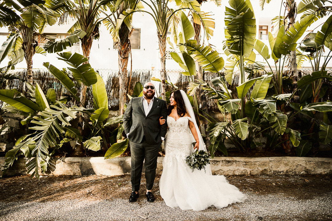 alternative bride and groom portrait shot in ibiza with palm tree backdrop