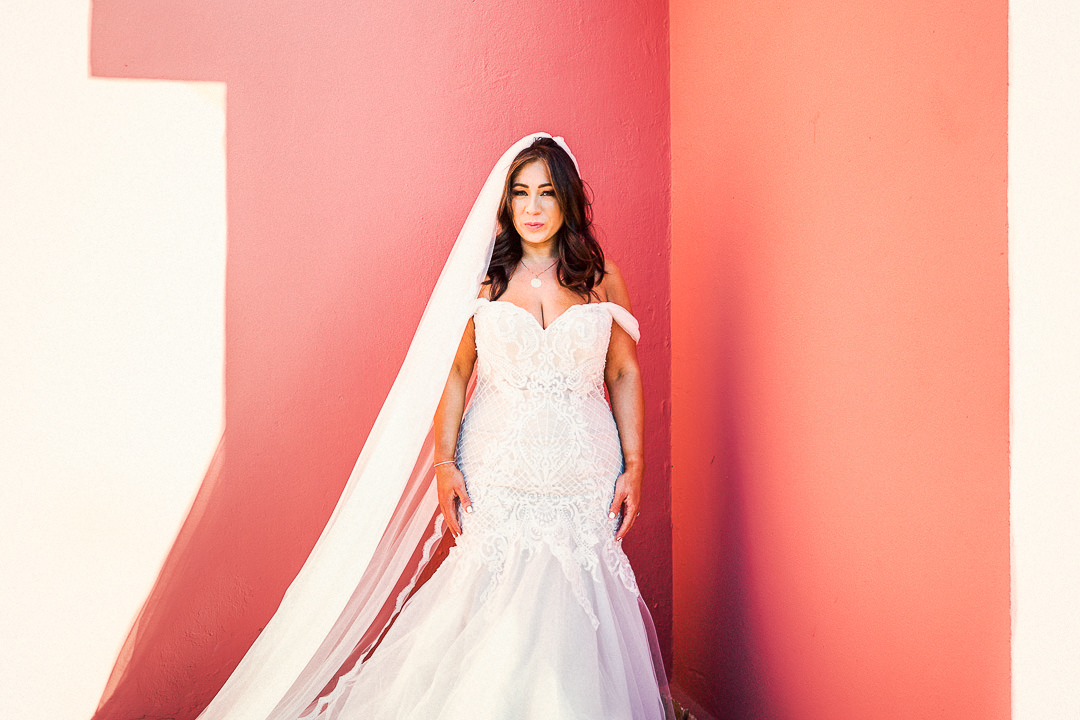 a bride stood against a pink wall in ibiza