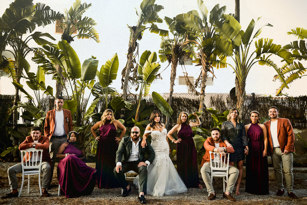a stylish and alternative wedding group shot with palm trees in ibiza