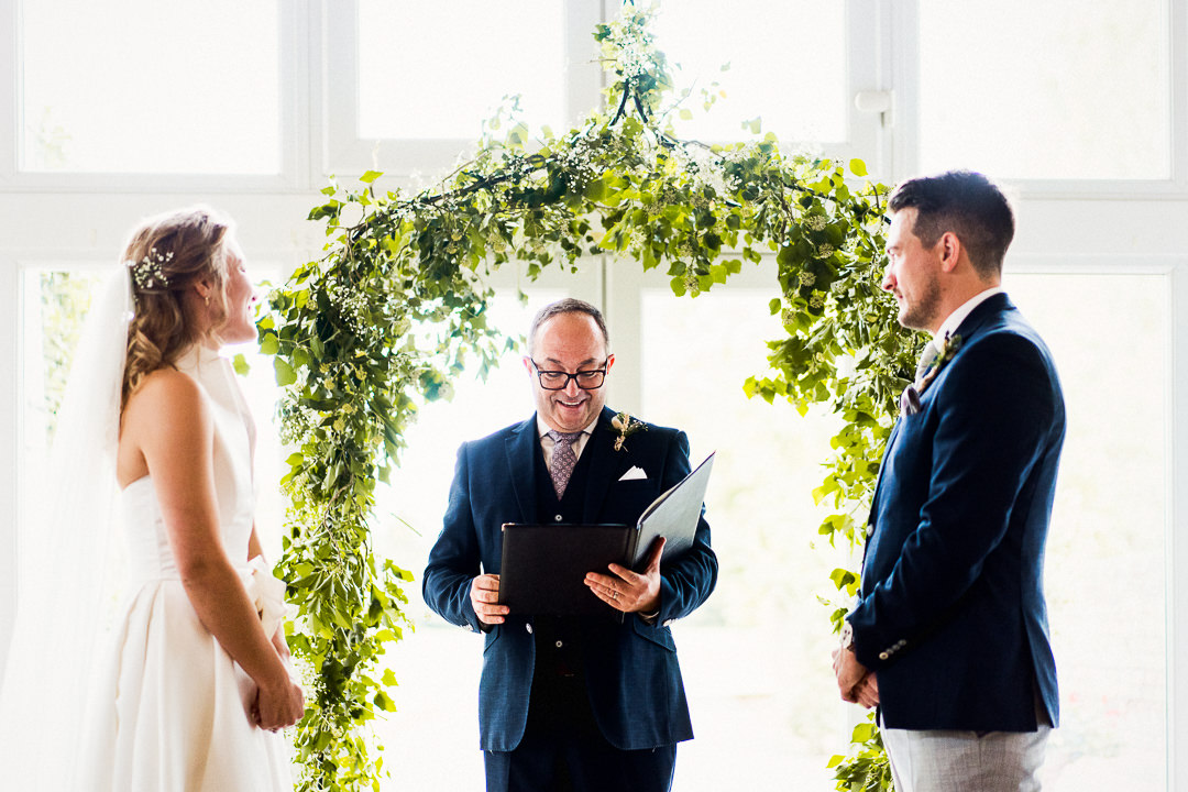 bride and grooms friend acts as celebrant in front of floral arch at lillibrooke manor