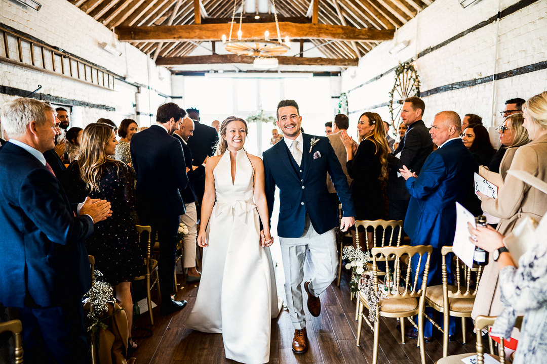 bride and groom exit ceremony in small barn at lillibrooke manor