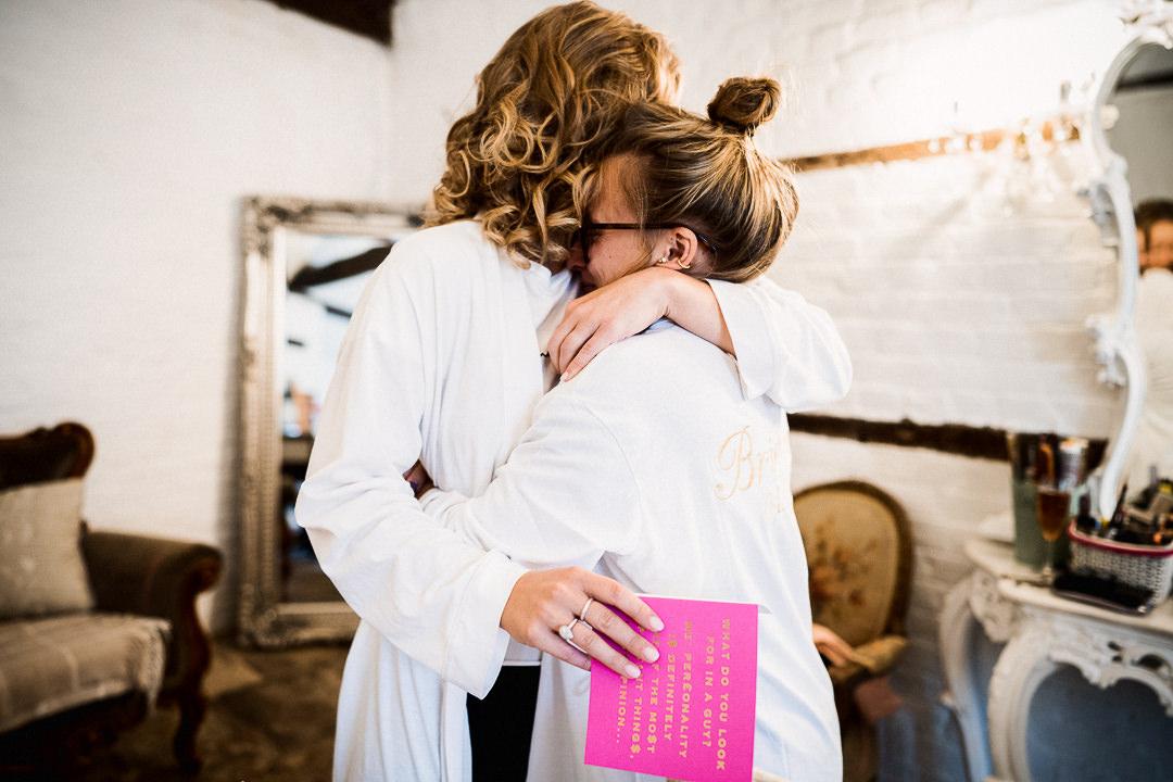 bride and her bridesmaid hug during bridal prep at lillibrooke manor
