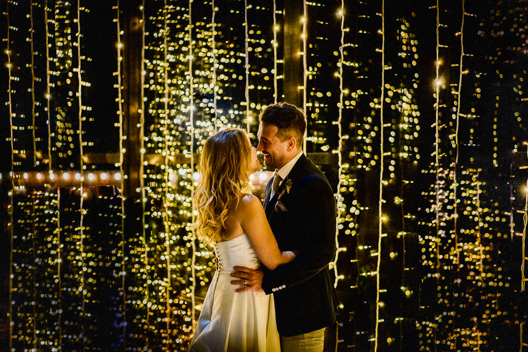 A bride and groom set against fairy lights at lillibrooke manor