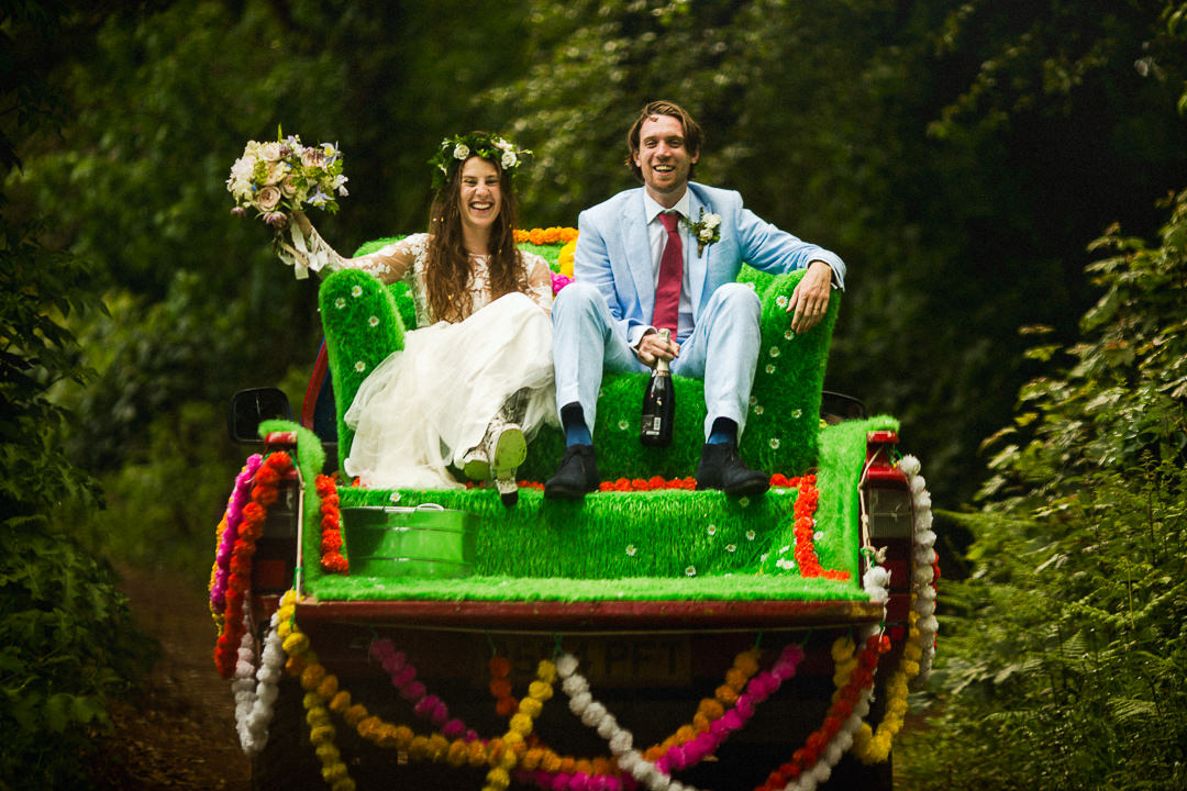 a wedding couple sit on a sofa attached to a pick up truck on their wedding day