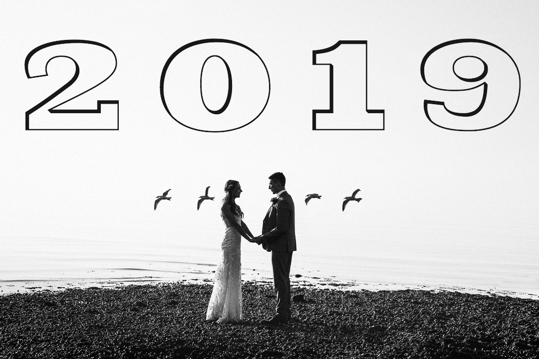 a couple face each other hand in hand for an alternative wedding photograph by the sea in whitstable. 4 gulls pass and frame them against the white sky