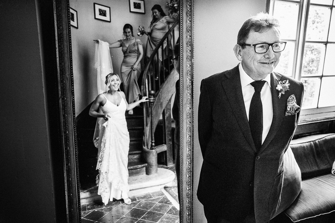 a father of the bride sees his daughter come down a stair at chateau lartigolle in France
