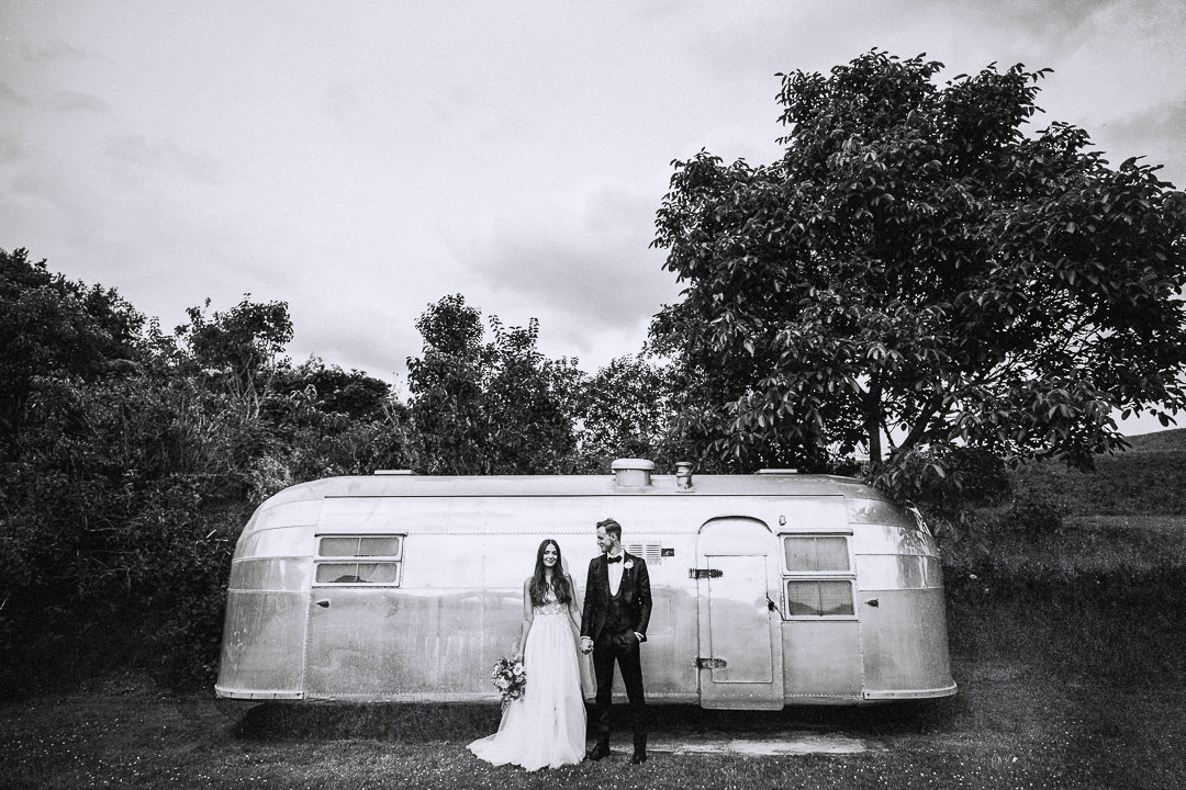 a couple posing in front of an airstream caravan