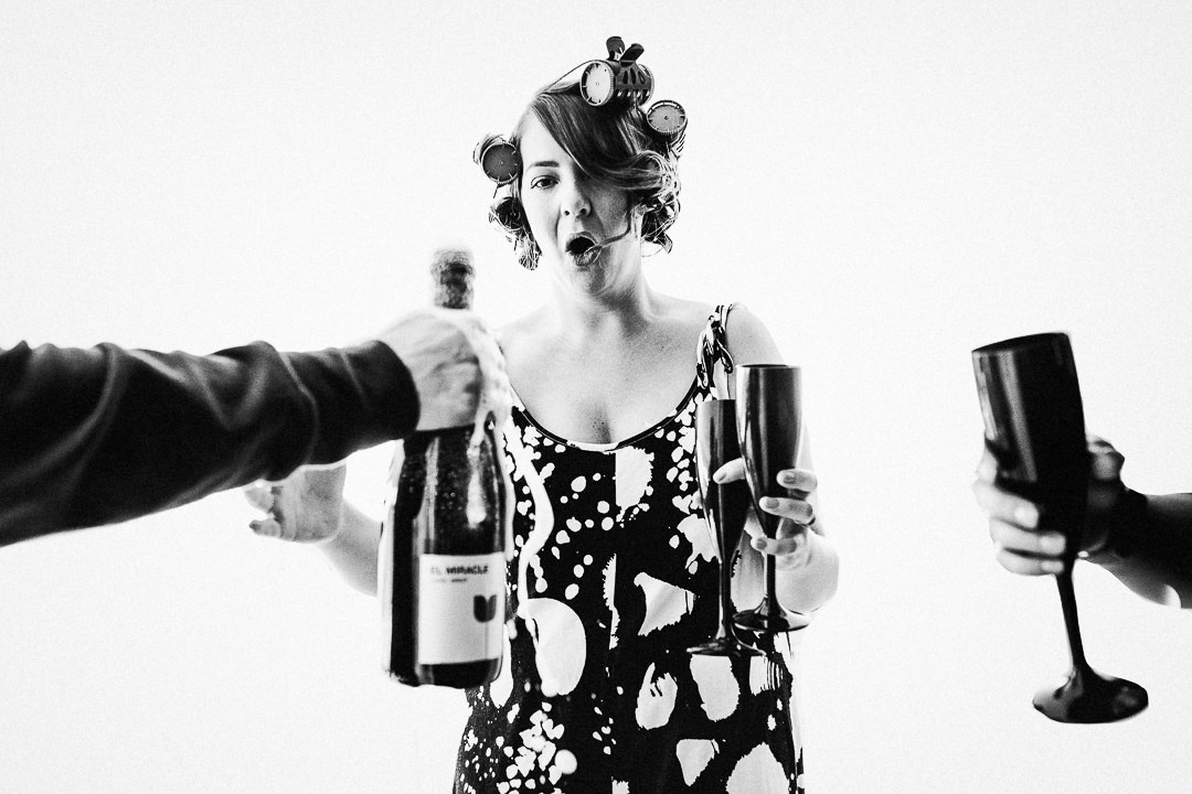 a bridesmaid reacts to a champagne bottle over flowing whilst she awaits with champagne flutes