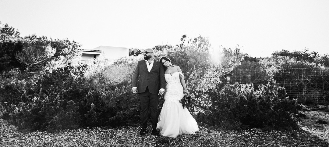 a portrait of a couple shot against strong light and shrub on a clifftop in ibiza