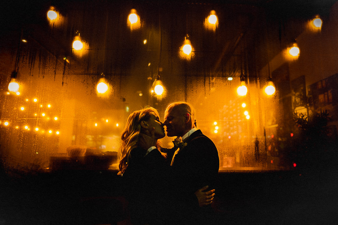 A wedding couple embrace in front of steamed up shop window lit by light bulbs on a London high street