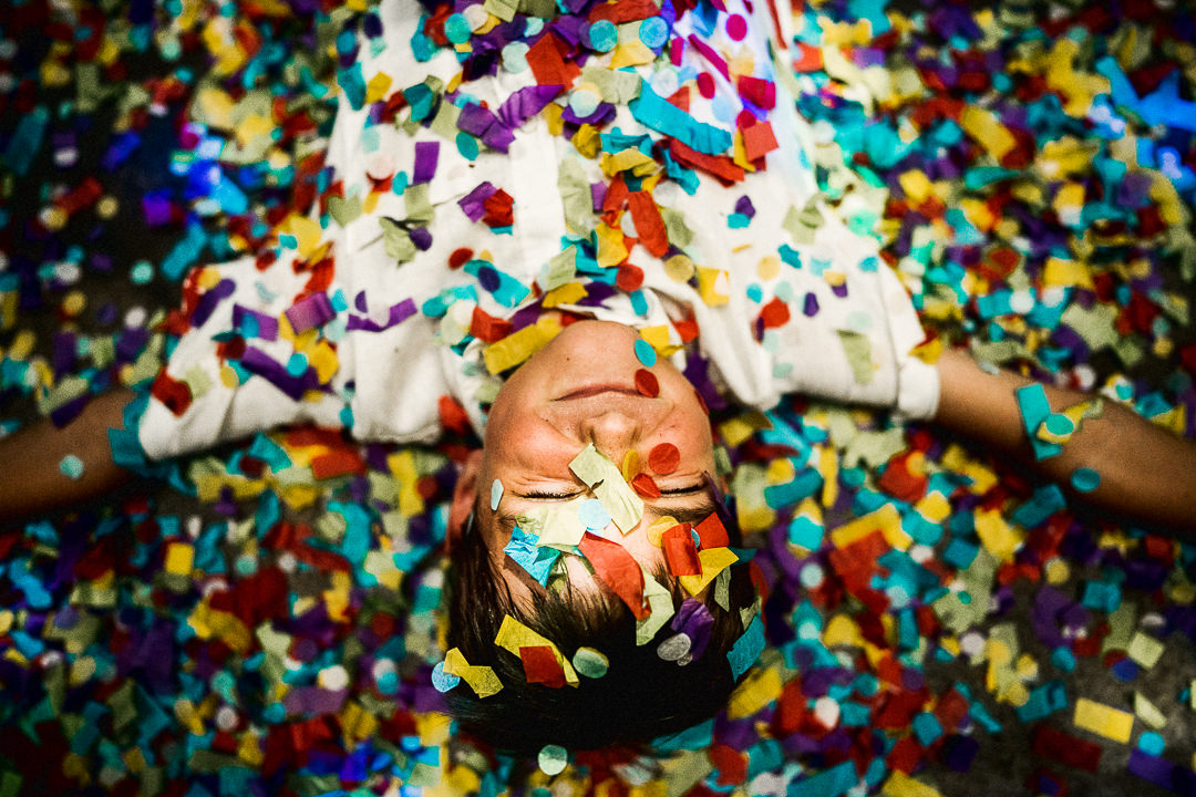 a boy at a wedding lies in a carpet of confetti