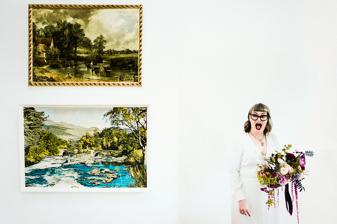 a bride reacts excitedly pre wedding ceremony against a white wall, she is holding her bouquet