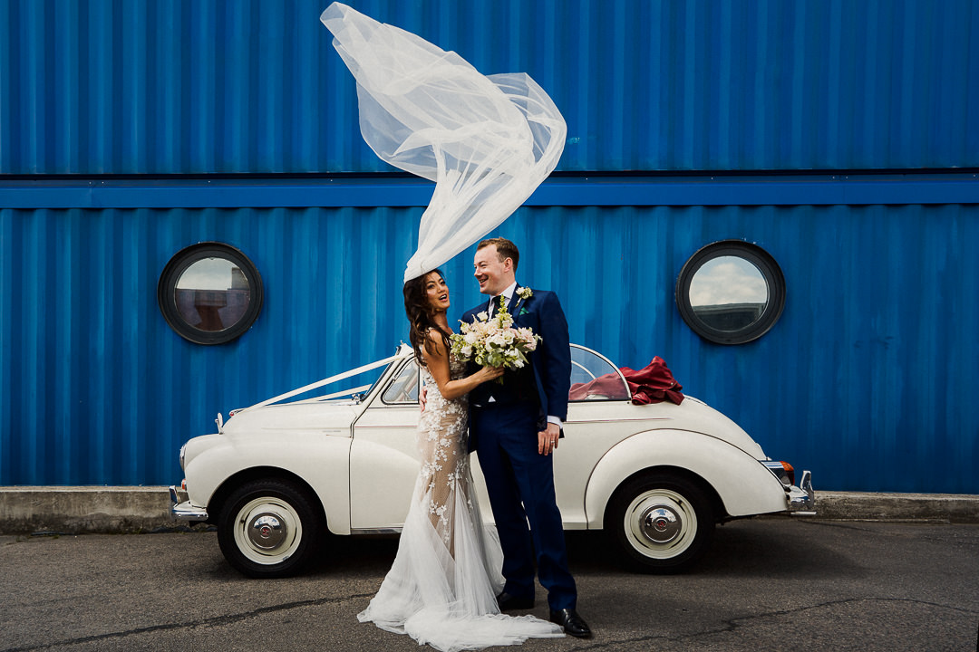 a brides veil blows upwards before a portrait with her husband and wedding car against a blue wall at trinity buoy wharf